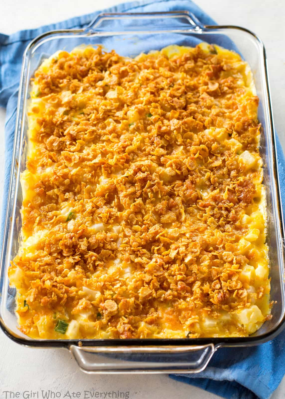 Gooey Potatoes - creamy, cheesy potatoes topped with buttery crunchy cornflakes. Some people call these funeral potatoes but this name is much less morbid. the-girl-who-ate-everything.com