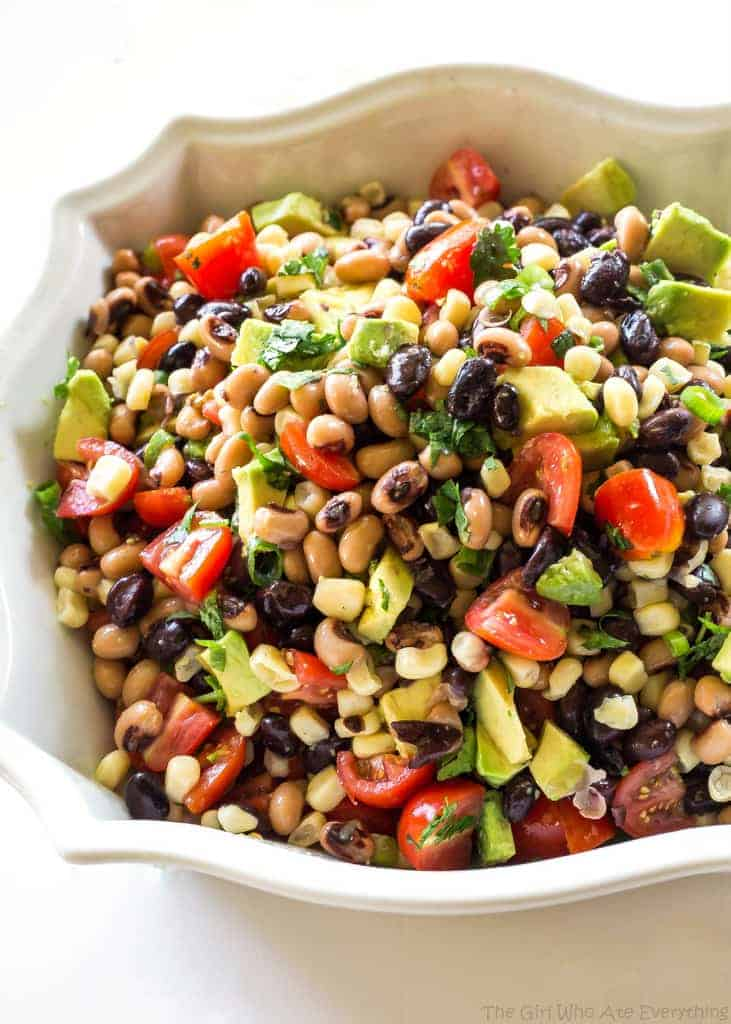 Cowboy Caviar - One of our favorite appetizers. Beans, avocado, tomatoes, and corn tossed in a light dressing. the-girl-who-ate-everything.com