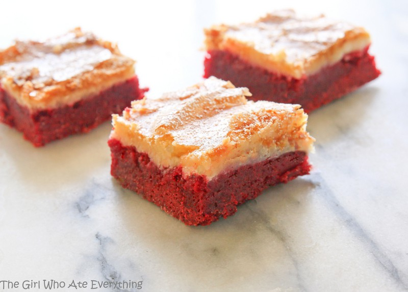 These Red Velvet Gooey Butter Bars are moist red velvet cake topped with a buttery cream cheese layer. Great for Halloween, Christmas, Valentine's Day, or the Fourth of July. the-girl-who-ate-everything.com