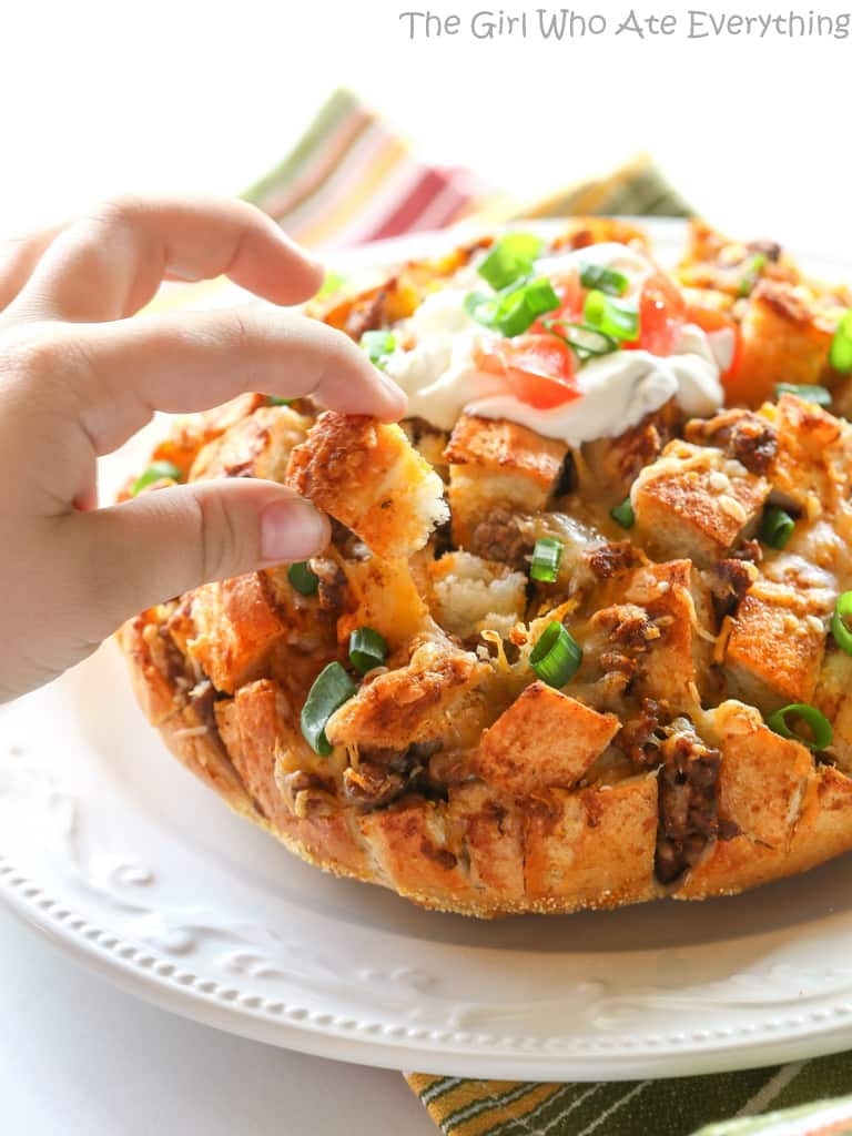 Taco Party Bread - A fun appetizer made with sourdough bread stuffed with taco meat, cheese, and topped with your favorite taco fixings. the-girl-who-ate-everything.com