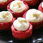 Mini Red Velvet Cheesecakes - moist red velvet cheesecake with an Oreo crust. Topped with cream cheese for the ultimate indulgence. Great for Christmas or Valentine's Day. the-girl-who-ate-everything.com