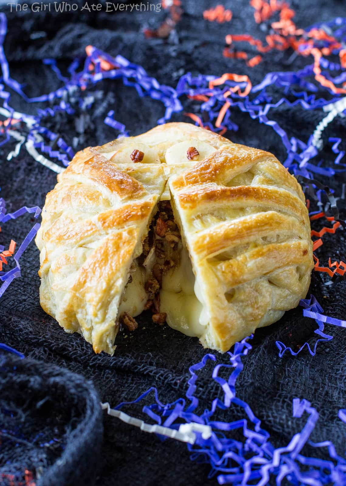 Mummy Wrapped Brie - topped with brown sugar and cinnamon pecans, baked inside puff pastry until nice and gooey. The best appetizer for Halloween! the-girl-who-ate-everything.com