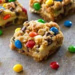 These Monster Cookie Cheesecake Bars have a layer of peanut butter, chocolate chips, oats, and M&M cookie bar with a layer of cheesecake in the middle.