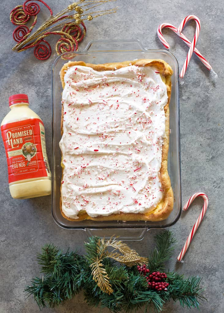 This Eggnog Éclair Cake is a unique holiday dessert with a cream puff crust, creamy eggnog layer, and topped with fresh cream and crushed peppermint candies.