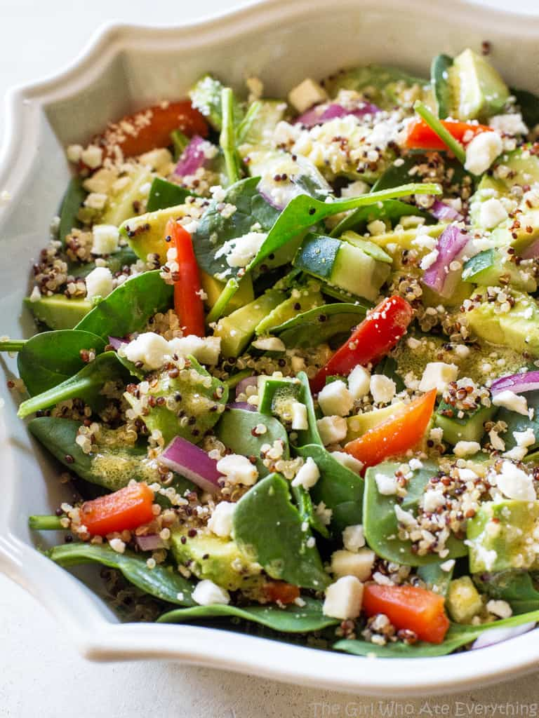 Spinach Quinoa Salad - full of rich healthy foods like cucumber, red bell pepper, avocado, and onion. This recipe is topped with a lemon dijon vinaigrette. the-girl-who-ate-everything.com