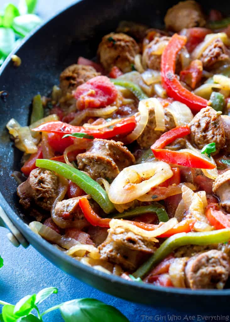 sliced sausage, green and red bell peppers and onions in a pan