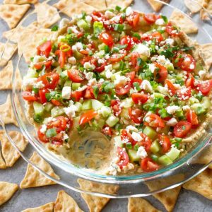Mediterranean 7-layer dip in a pie plate with pita chips