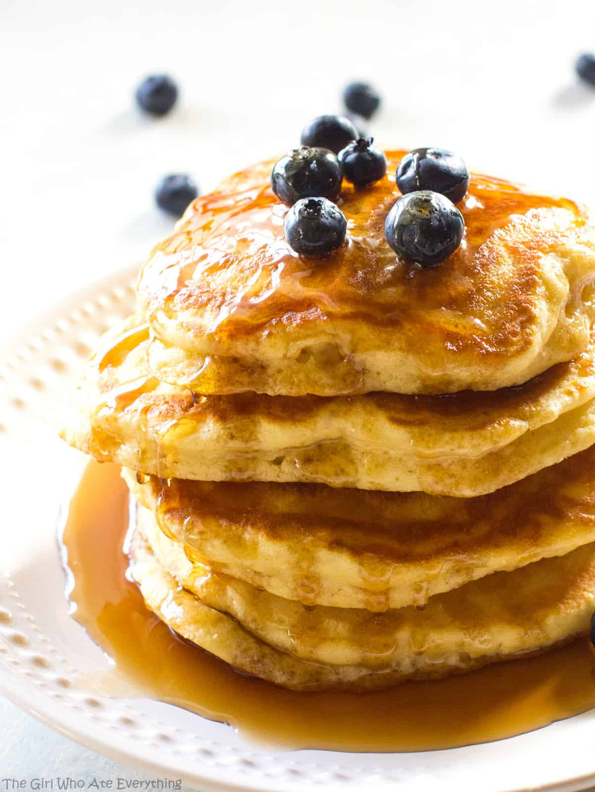 Fluffy pancakes and blueberries with syrup on a plate