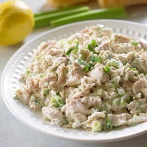 chicken salad on a white plate with a lemon